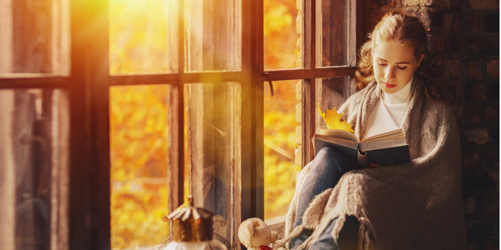 happy-young-woman-reading-book-by-window-in-fall-picture-id607482164