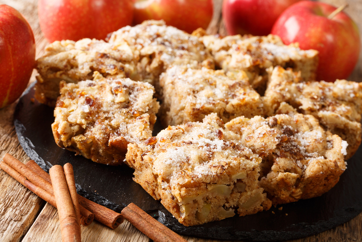 Apple Bars are a perfect Autumn dessert that mixes apple pie and blondies close-up on a slate board. horizontal