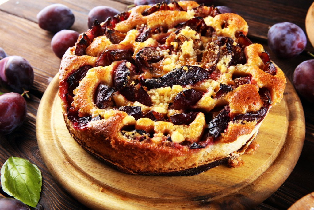 rustic-plum-cake-on-wooden-background-with-plums-around-picture-id1280787321