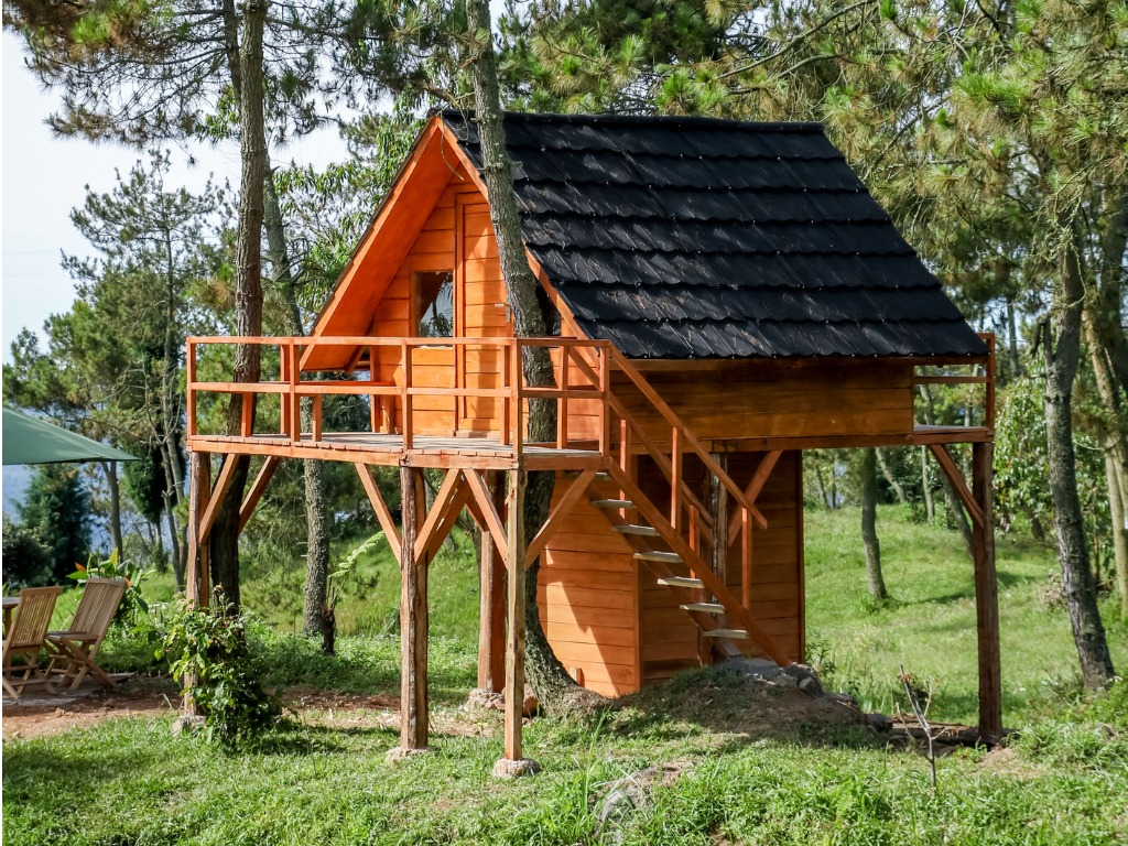 wooden-tree-house-in-the-middle-of-a-forest-for-glamorous-camping-picture-id970012232
