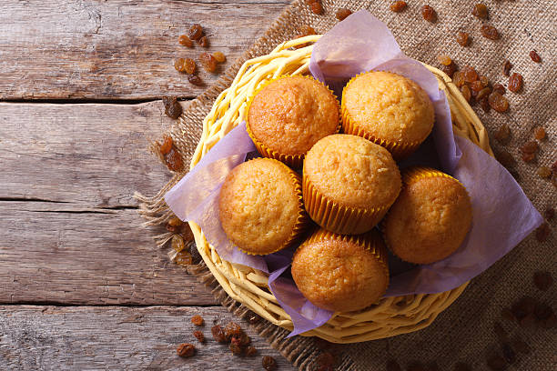 Orange muffins in a basket on an old table. top view of a horizontal